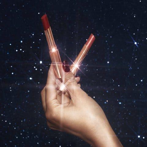 hand holding charlotte tilbury lipsticks